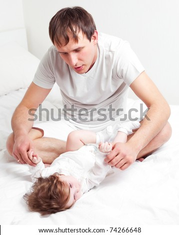 young father with his six months old daughter on the bed at home - stock photo