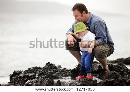 Young father with little son outdoors at ocean - stock photo