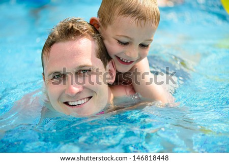 Young father with little son swimming in pool