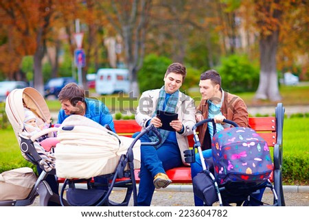 young fathers with baby strollers on city walk - stock photo