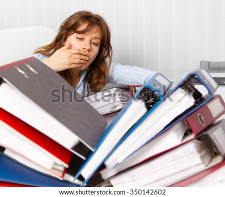 Young female accountant. Attractive and tired, over worked with too much book keeping to do. - stock photo