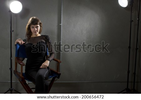 young female actress sitting on a directors chair - stock photo