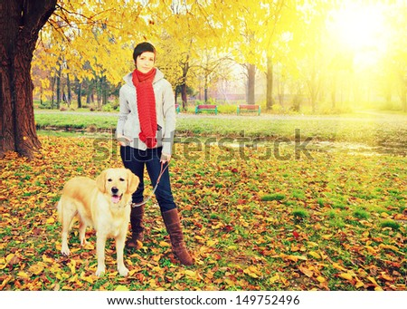 Young female and her dog (Labrador retriever) posing in autumn in a city park on a sunny day - stock photo