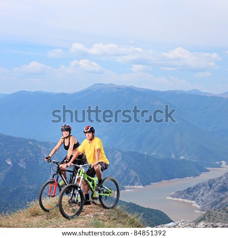 Young female and male posing with a mountain bikes with lake in the background - stock photo
