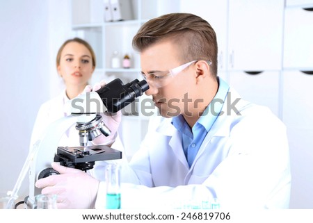 Young female and male scientists  with microscope in laboratory - stock photo