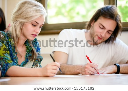 Young female and male student at class - stock photo