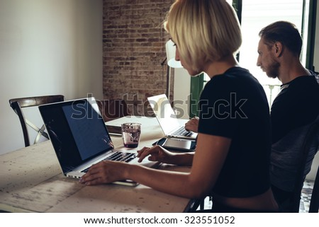 Young female and young man freelancers work with laptops in a loft interior.