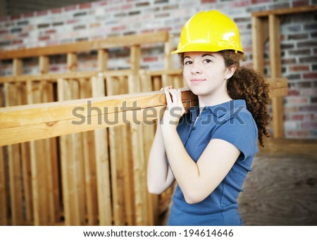Young female apprentice carrying boards on a construction site.   - stock photo