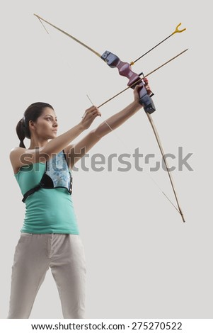 Young female archer practicing archery against gray background