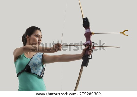 Young female archer with bow and arrow against gray background