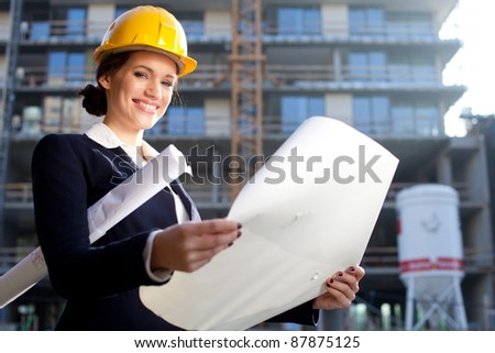 Young female architect/construction engineer at a construction site - stock photo