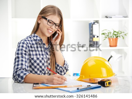 Young female architect consultant talking on phone in the office. Woman designer working on blueprint of industrial project.  - stock photo