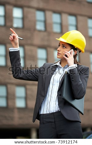 young female architect in hard hat talks over mobile phone and point to the building in front of her - stock photo
