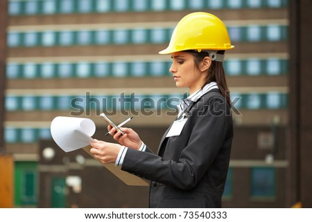 young female architect in yellow hard hat check her mobile phone, construction site - stock photo