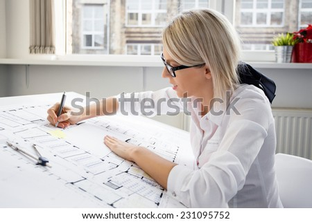 Young female architect working on blueprint - stock photo