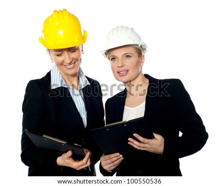 Young female architects reviewing documents. Discussing solution - stock photo