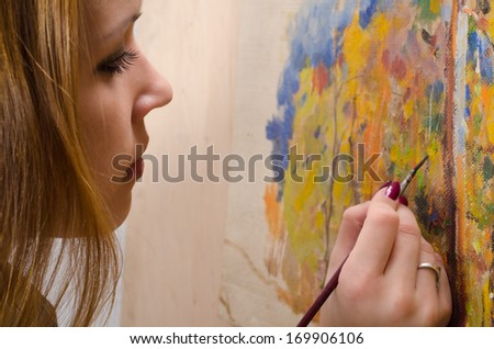 Young female artist painting in her studio. - stock photo