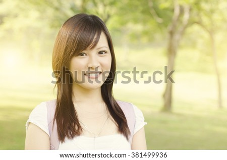 Young female Asian university student standing on campus lawn, with backpack and smiling. - stock photo