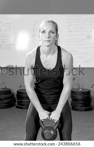 young female athlete exercising with kettlebell at the gym - focus on the woman