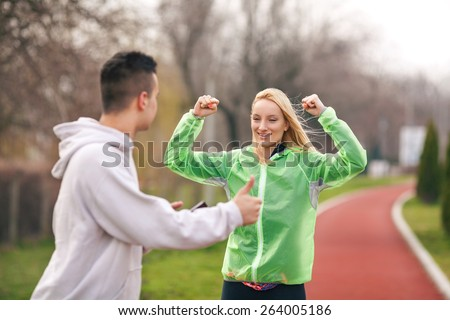 Young female athlete happy to achieve the goal celebrating with her coach - stock photo