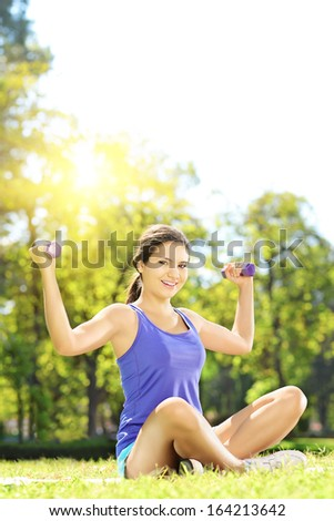 Young female athlete in sportswear exercising with dumbbells in a park - stock photo