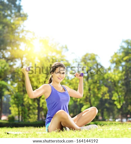 Young female athlete in sportswear exercising with dumbbells in a park, shot with a tilt and shift lens