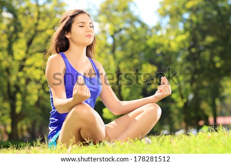 Young female athlete in sportswear meditating seated on a green grass in a park - stock photo