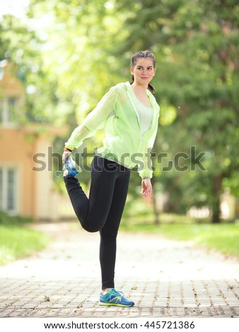 Young female athlete is doing stretching exercise in nature. She is standing on one leg and holding the other, stretching her thigh. - stock photo