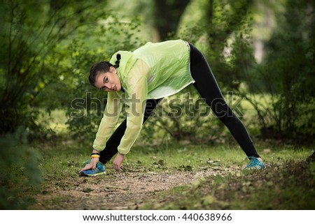 Young female athlete is exercising in nature. She is leaning over her leg, stretching thigh and looking at camera. - stock photo