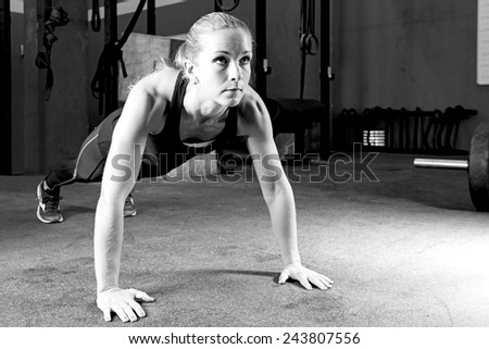young female athlete is making push-ups at the gym - focus on the woman - stock photo