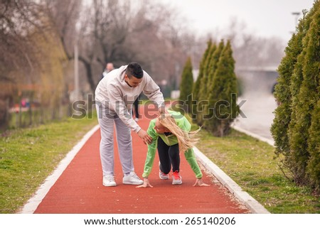 Young female athlete practicing with her coach on running track - stock photo