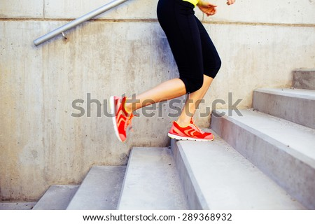 Young female athlete running up the stairs - stock photo