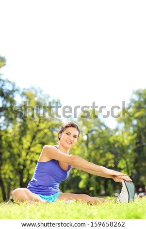 Young female athlete sitting on an excercising mat and stretching in a park - stock photo