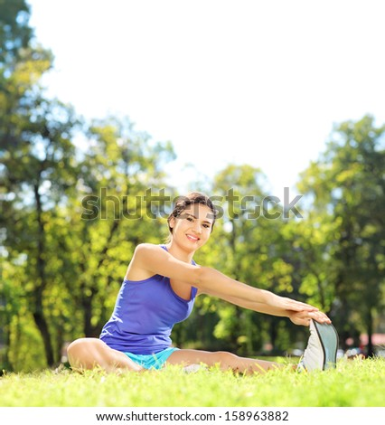 Young female athlete sitting on an excercising mat and stretching in a park, shot with a tilt and shift lens - stock photo