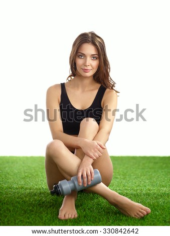 Young female athlete sitting on grass after exericise and holding a water bottle - stock photo