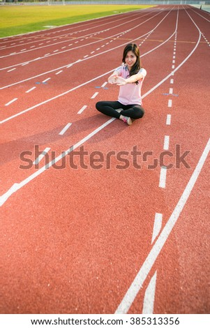young female athlete stretching and warming up on a running track in a stadium.