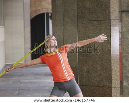 Young female athlete throwing javelin in portico - stock photo