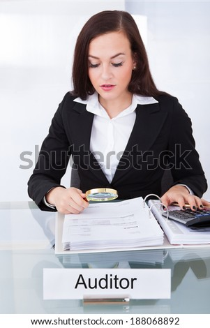 Young female auditor scrutinizing financial documents at desk in office - stock photo
