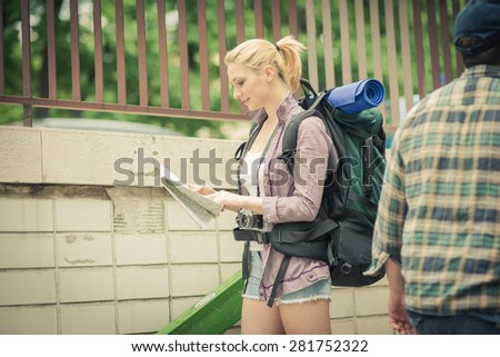Young female backpacker using map in the city - stock photo