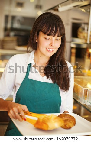 young female baker making bread - stock photo