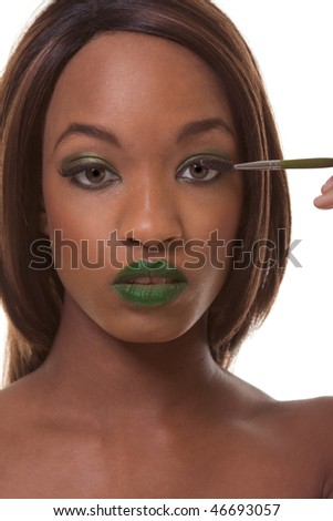 Young female beauty ethnic fashion model of African-American ethnicity with green lips and eye shades covered in dramatic make-up and holding makeup brush - stock photo