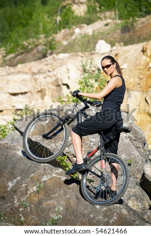 young female biker athlete resting up in a mountains - stock photo