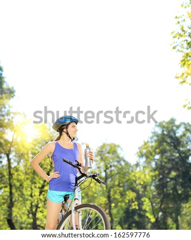 Young female biker posing on a mountain bike outdoors on a sunny day, shot with a tilt and shift - stock photo