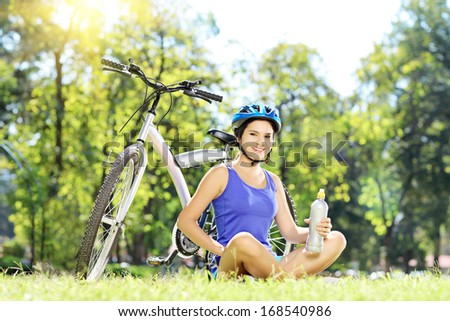 Young female biker sitting on a green grass next to her bike in a park