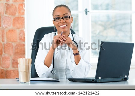 Young female black doctor sitting at a window in clinic, she has a stethoscope - stock photo