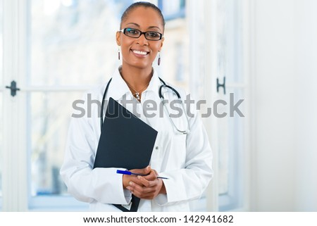 Young female black doctor standing at a window in clinic with a file or dossier - stock photo