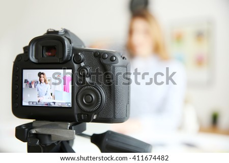 Young female blogger on camera screen - stock photo