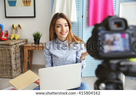 Young female blogger with laptop and book on camera screen - stock photo