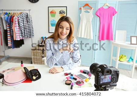 Young female blogger with makeup cosmetics recording video at home - stock photo