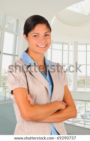 Young female business professional in modern office building with her arms folded. She is smiling in 3/4 view. Vertical format.